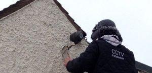CCTV engineer up a ladder